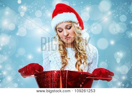 Frustrated and annoyed beautiful young woman in Santa Claus hat with a gift on a blue background poster