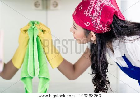 Asian homemaker cleaning the home with cloth