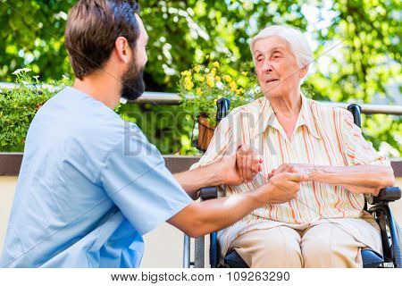 Geriatric nurse holding hand of old woman in rest home