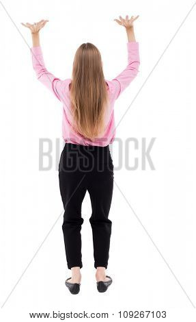 back view of business woman  protects hands from what is falling from above.  Isolated over white background. girl office worker in black trousers raised her arms above her head fingers spread.
