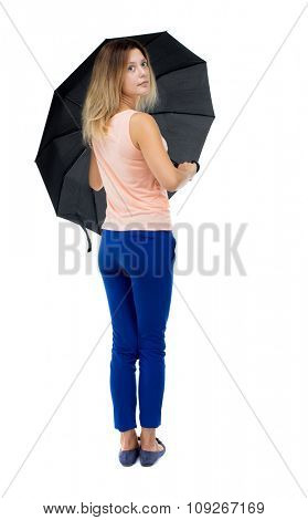 young woman under an umbrella. Rear view people collection.  backside view of person.  Isolated over white background. Blonde girl in blue pants stands with an umbrella in retrospect.