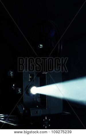 Film projector. Cinema projector light beam - ray of light Film reel on retro film projector.