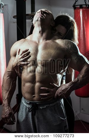 Woman Passionately Embraces Muscular Man In The Gym
