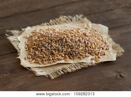 Pile of whole unpolished spelt on wooden table poster