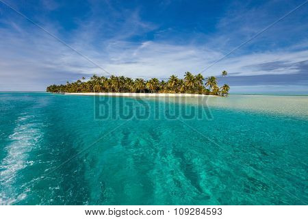 Stunning tropical Aitutaki One Foot island with palm trees, white sand, turquoise ocean water and blue sky at Cook Islands, South Pacific