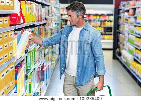 Handsome father picking box of cereals at supermarket