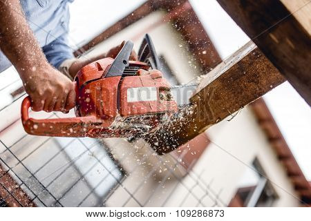 Worker Using A Chainsaw For Cutting Timber Wood, Construction Material, Trimming And Slicing Logs