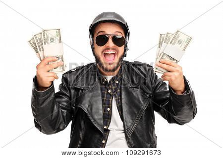 Happy young male biker holding few stacks of money and looking at the camera isolated on white background