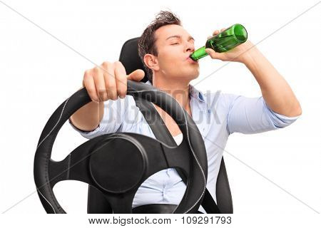 Studio shot of a young irresponsible driver driving and drinking a beer isolated on white background