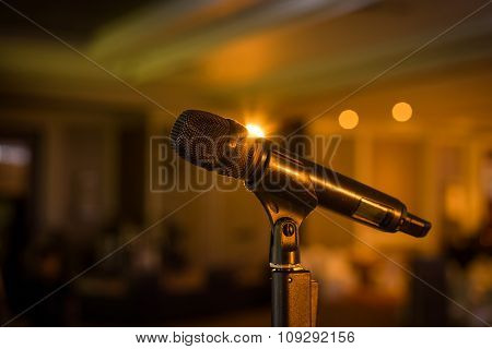 Wireless microphone stand on the stage venue with blur bokeh background poster