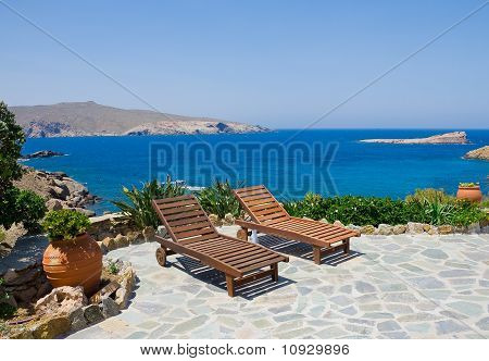 Garden With Sun Loungers On The Background Of The Sea. Mykonos. Greece.