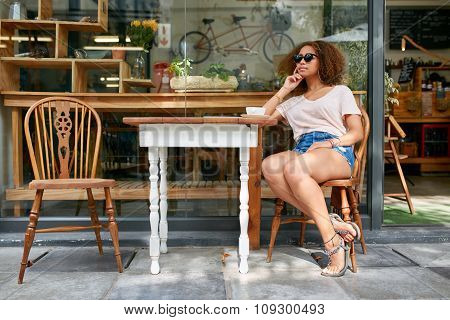Young African Woman Sitting At Coffee Shop