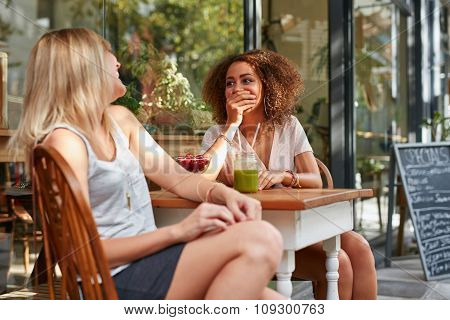 Two Young Girls Chatting And Laughing At Cafe