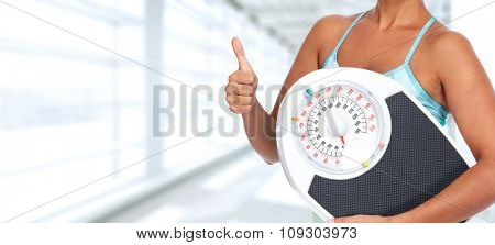 Young woman with scales. Healthy diet and weight loss.
