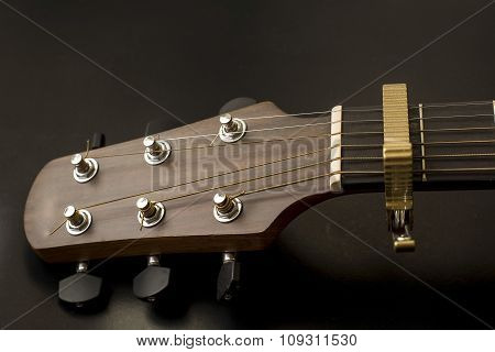 Headstock,fret,capo,bordfrets, tuners of guitar acoustic isolate on the black ground.