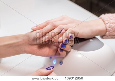 Manicurist apply foundation before paint shellac