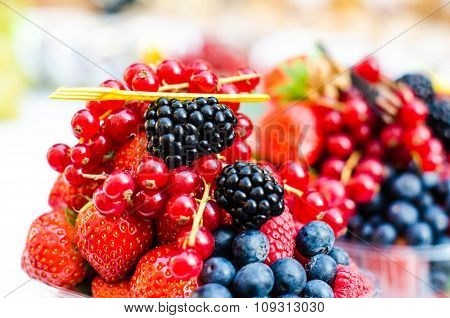 Forest fruits like a blueberries, raspberries, strawberries, red currants on a market. On a white ta