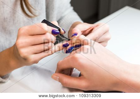 Manicurist put black shellac on the fingernails
