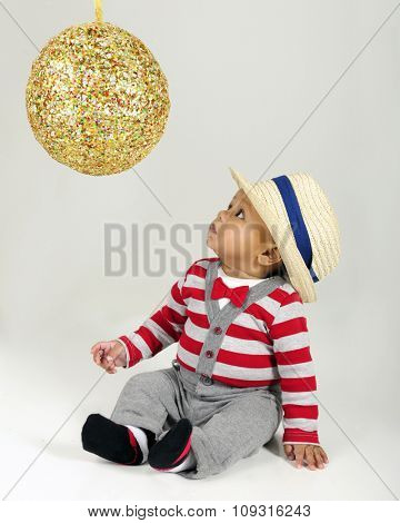 an adorable baby boy looking up skeptically at a big, sparkly Christmas ornament.  On a gray background.