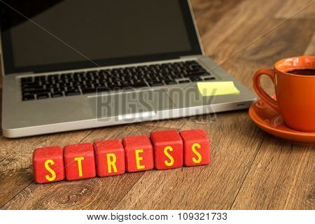 Stress written on a wooden cube in a office desk