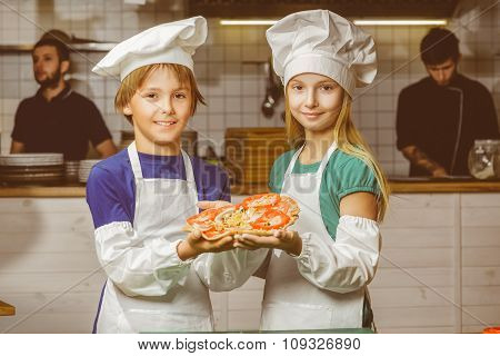 Funny happy chef boy and girl cooking at restaurant kitchen or show pizza