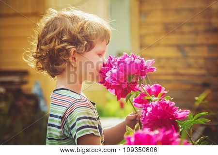 Child Smelling Bouquet Of Peonies, Sun Backlighting. Toning Photo.