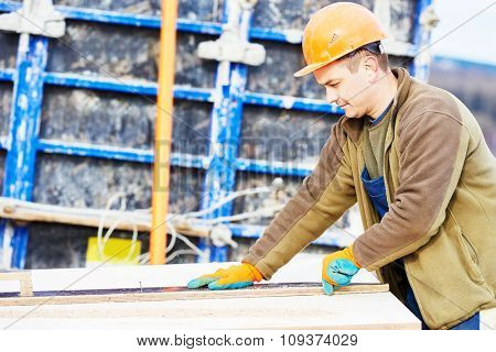 Concrete work. Male builder carpenter worker cutting plywood for falsework construction before concreting at building site