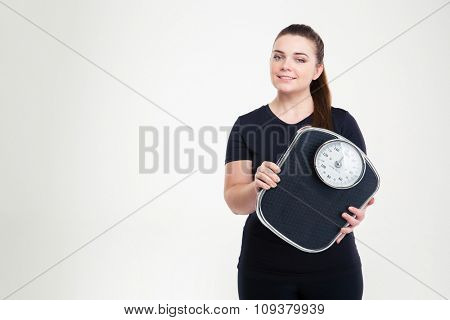 Portrait of a happy fat woman holding weighing machine isolated on a white background