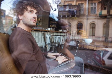 Smiling content curly young male in brown sweetshirt using laptop in cafe and dreaming
