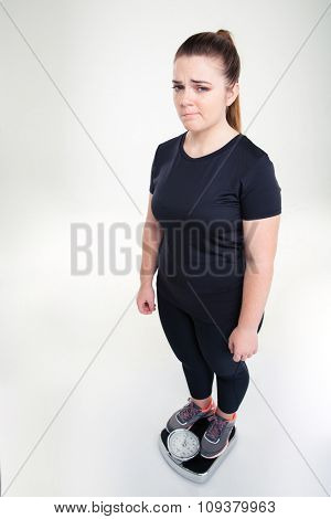 Full length portrait of a sad fat woman standing on weighing machine isolated on a white background