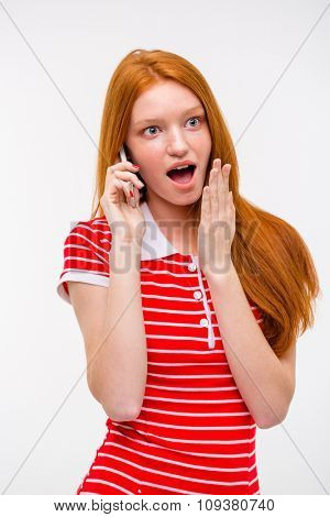 Amazed excited pretty attractive redhead woman with long hair talking on mobile phone