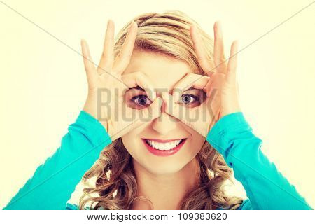 Portrait of a woman showing ok sign on eyes.