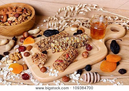 Fitness bars with granola oatmeal nuts dried fruit and honey on the table poster