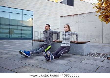 fitness, sport, training, people and lifestyle concept - couple doing triceps dip exercise on bench outdoors poster