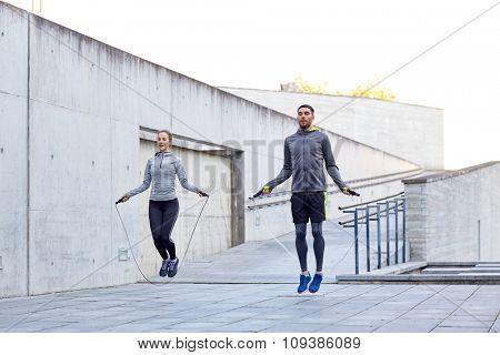 fitness, sport, people, exercising and lifestyle concept - man and woman skipping with jump rope outdoors