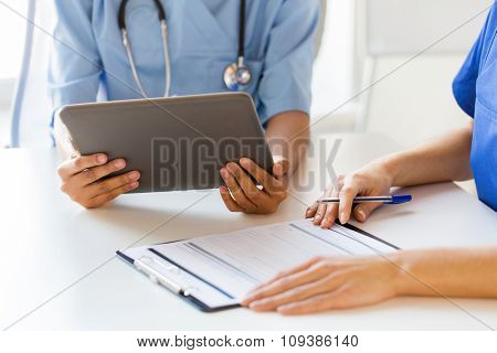 hospital, profession, people and medicine concept - close up of doctors with tablet pc computer and clipboard meeting at medical office