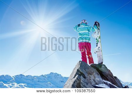 Back view of female snowboarder wearing helmet, blue jacket, gloves and pink pants standing with snowboard and looking at sunny alpine mountain landscape covering her eyes - winter sports concept