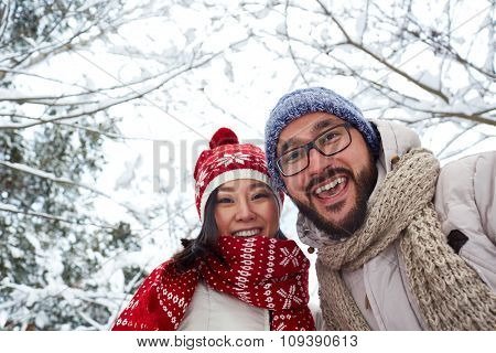 Happy young couple in winterwear looking at camera outdoors