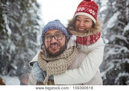 Asian couple in winterwear laughing outdoors