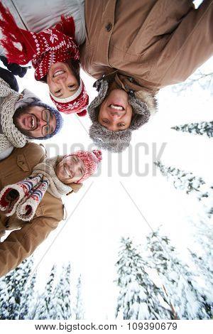 Joyful friends in winterwear spending time in park
