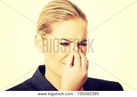 Woman pinching her nose because of disgusting smell. poster