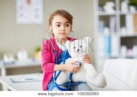 Little girl with stethoscope examining her teddybear