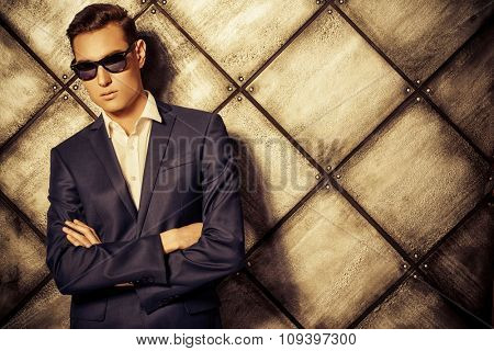 Fashion shot of a handsome young man in elegant classic suit and sunglasses. Toned photo, sepia.
