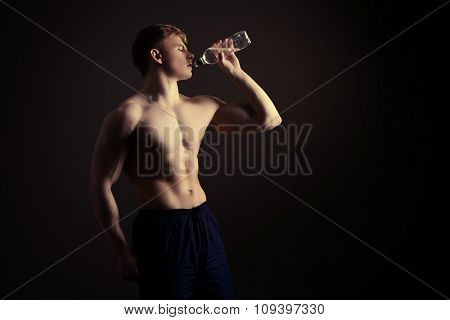 Athletic man drinking clear water after exercise. Sports, healthcare. poster