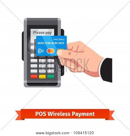Man holding credit card paying over POS terminal
