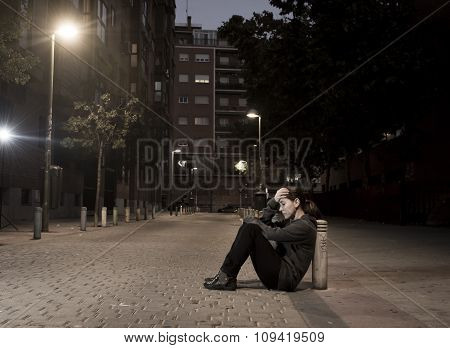 young sad woman sitting on street ground at night alone desperate suffering depression left abandoned and lost in grunge urban background as abuse and violence female victim or addict concept poster