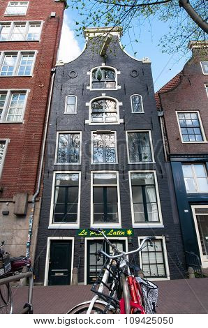 AMSTERDAMNETHERLANDS-APRIL 27: Tipical Amsterdam architecture and appartments with bike in foreground on April 27 2015 in Amsterdam Netherlands.