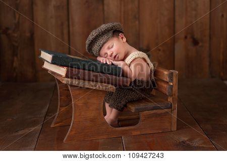 Newborn Baby Boy Sleeping At His School Desk