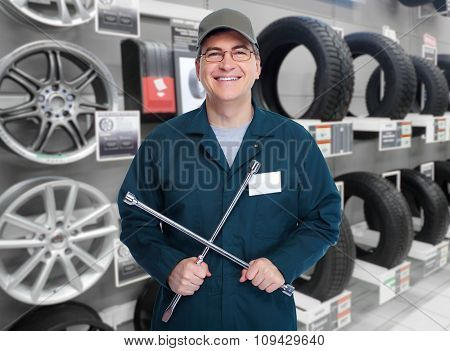 Smiling car mechanic with lug wrench over garage background.