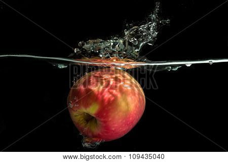 studio picture concept. Apple dropped into a container of water to obtain a water splash interesting